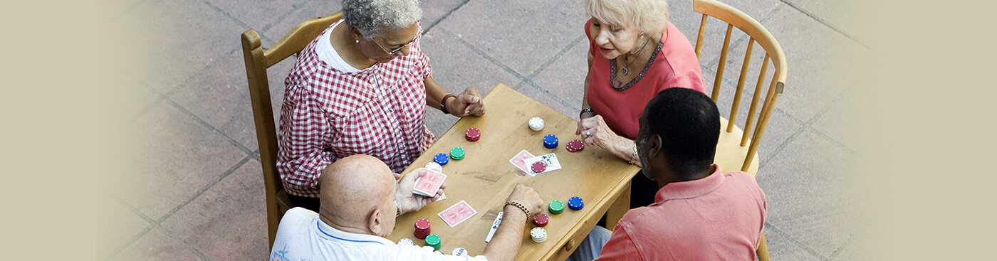 Four senior citizens playing a card game