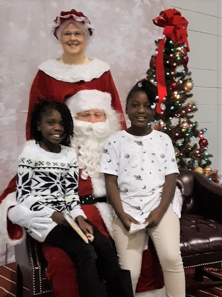 2 little girls on Santa's lap with Mrs. Claus standing behind him